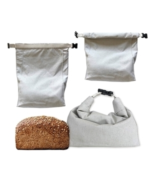 3 white bags made from hemp fabric next to a loaf of bread