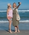 Two ladies taking a selfie on the beach, one of them carrying the hemp twine moon beach bag